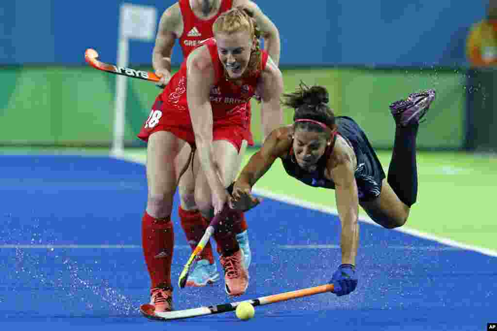 United States' Melissa Gonzalez, right, falls while fights for the ball with Britain's Nicola White during a women's field hockey match at the 2016 Summer Olympics in Rio de Janeiro, Brazil, Aug. 13, 2016.