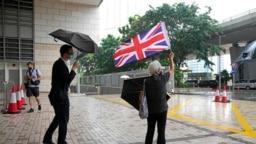 Seorang aktivis prodemokrasi Alexandra Wong memegang bendera Inggris Raya dalam persidangan beberapa aktivis di Hong Kong yang dituntut dengan tuduhan subversi pada 23 September 2021. (Foto: AP/Kin Cheung)