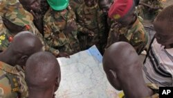 Soldiers from the Sudan People's Liberation Army (SPLA) examine a map at the frontline position in Pana Kuach, Unity State, South Sudan, Friday May 11 2012. In late April, tensions between Sudan and South Sudan erupted into conflict along their poorly def