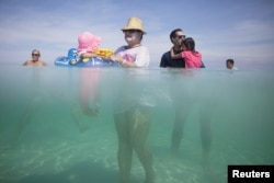 FILE - Retiree Madeline Barcelo (C) holds her granddaughter surrounded by relatives at the beach in Varadero, Cuba, Aug. 26, 2015.