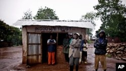 Residents stand outside a shop that was looted by Congolese soldiers during a mass rape and looting campaign in the town of Fizi, Democratic Republic of Congo, February 18, 2011