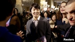 폴란드 바르샤바에서 열린 국제 쇼팽 피아노 콩쿠르에서 한국인 피아니스트 조성진 씨가 21일 우승자 발표와 함께 주변의 축하를 받고 있다.