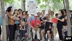 资料照:一组退休人员在北京公园里唱红歌。