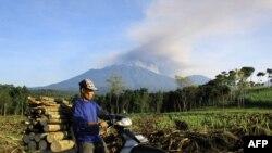 Seorang warga mengendarai sepeda motornya sambil membawa kayu bakar, melewati wilayah Banyuwangi dengan latar belakang gunung Raung yang mengepulkan asap dan mengeluarkan abu vulkanik (21/7).