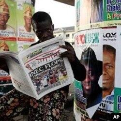Un Nigérian lisant un journal parlant des difficultés de la commission électorale nationale