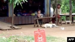 Trẻ em ngồi gần một bãi mìn bên ngoài căn nhà ở tỉnh Battambang, tây bắc Campuchia