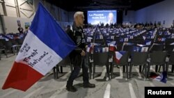 A supporter holds a French flag before a political rally of Marion Marechal-Le Pen, French National Front political party candidate for the second round of regional elections in Marseilles, Dec. 9, 2015.
