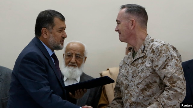 International Security Assistance Force (ISAF) commander General Joseph Dunford (r) and Afghan Defense Minister Bismillah Khan Mohammadi  during a ceremony handing over the Bagram prison to Afghan authorities, at the U.S. airbase in Bagram, Mar 25, 2013.