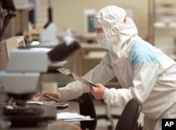 """芯片技术人员在台湾联华电子公司(UMC)的""""洁净室""""测试设施检查硅片(资料照)"""
