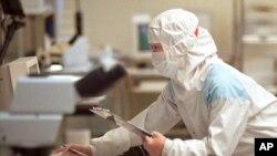 """芯片技術人員在台灣聯華電子公司(UMC)的""""潔淨室""""測試設施檢查硅片(資料照片)"""