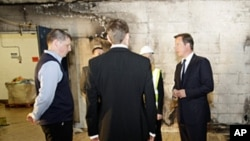 Britain's Prime Minister David Cameron (r) visits a looted Liddell supermarket in Salford, England, Aug. 12, 2011