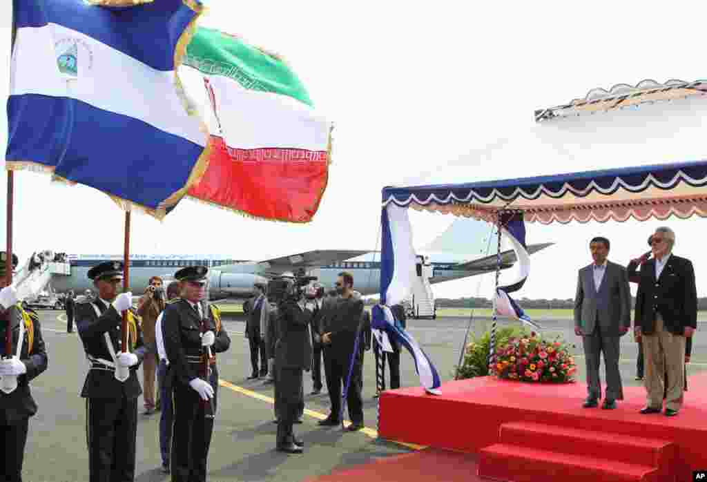 Mr. Ahmadinejad and Nicaragua's Foreign Minister Samuel Santos (R) stand next to their national flags upon the Iranian president's arrival in Managua January 10, 2012. (Reuters)