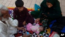 Family members surround a child suffering from dehydration due to severe heat, at a local hospital in Karachi, Pakistan, June 23, 2015.