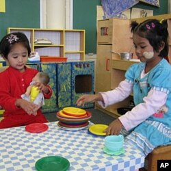 Girls play dinner-time with a doll