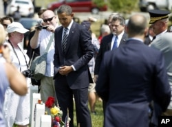FILE - Then-President Barack Obama talks to family members of fallen soldiers near the graves in Section 60 of Arlington National Cemetery, in Arlington, Virginia, May 30, 2011.