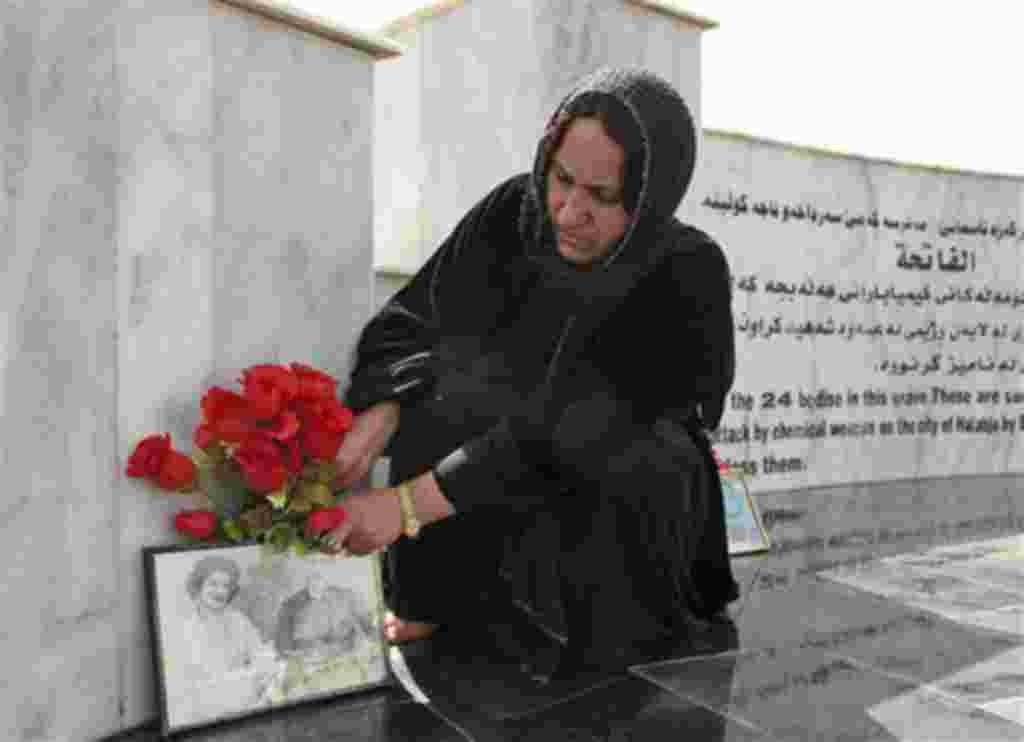 Kurdish woman lays flowers at a monument for the victims of Halabja massacre on its 20th anniversary in Halabja, Iraq , Sunday, March 16, 2008. Some 5,600 people were killed when Saddam Hussein ordered the attack in Halabja as part of a scorched-earth cam