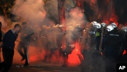 Montenegrin police officers are engulfed in smoke and flames as opposition supporters hurl torches toward them during a protest in front of the parliament building in Podgorica, Montenegro, Oct. 24, 2015.
