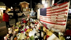 FILE - A U.S. flag displays the name of 26 victims killed Dec. 14, 2012, when Adam Lanza opened fired at Sandy Hook Elementary School in Newtown, Conn.