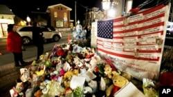 Bendera Amerika dan daftar korban penembakan massal menghiasi sudut kota Newtown, Connecticut (20/12). (Foto: AP)
