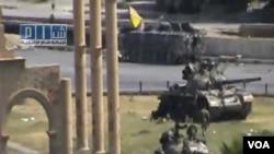 Pasukan Suriah dengan berkendaraan tank-tank melakukan patroli di pusat kota Hama (1/8).