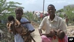 ຊາວໂຊມາເລຍ ກໍາລັງຫອບລູກທີ່ຂາດອາຫານຢ່າງຮ້າຍແຮງຂອງຕົນ ໄປປິ່ນປົວທີ່ໂຮງໝໍ ໃນເມືອງຫລວງ Mogadishu