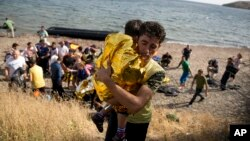 A Syrian man carries a child wrapped in a thermal blanket as they arrive with others at the coast on a dinghy after crossing from Turkey, at the island of Lesbos, Greece, Sept. 7, 2015.