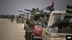利比亚反对派武装周日在布雷加城外查看地形