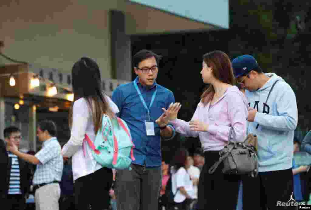 Personal electoral ayuda a un votante en un colegio electoral durante las elecciones locales del consejo de distrito en Hong Kong, China, el 24 de noviembre de 2019.