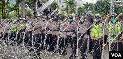 Kawat besi yang dijaga polisi di kawasan Patung Kuda, Jakarta yang membatasi jalan ke Istana Merdeka. (Foto: VOA/Sasmito Madrim)