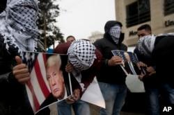 Người Palestine cầm áp phích có hình ảnh Tổng thống Mỹ Donald Trump trong cuộc biểu tình ở thành phố Ramallah ở Bờ Tây hôm 6/12 sau khi ông Trump tuyên bố kế hoạch công nhận Jerusalem là thủ đô của Israel.
