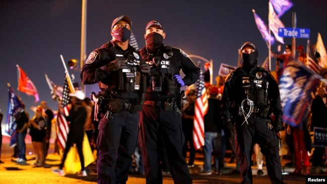 """North Las Vegas Police officers keep an eye on supporters of U.S. President Donald Trump during a """"Stop the Steal"""" protest at Clark County Election Center in North Las Vegas, Nevada, U.S. November 5, 2020. REUTERS/Steve Marcus"""