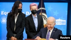 U.S. Women's National Soccer Team players Margaret Purce and Megan Rapinoe peek over U.S. President Joe Biden's shoulder as he signs an Equal Pay Day proclamation at the White House in Washington, U.S. March 24, 2021.