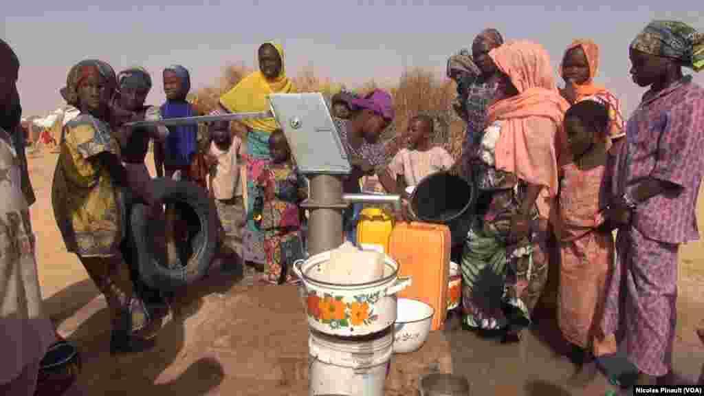 Mulheres e crianças tiram água de um poço em Assaga, no Níger. (VOA/Nicolas Pinault)