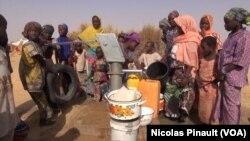 Des femmes et des enfants tirent de l'eau du puits dans le camp Assaga, à Diffa, au Niger, le 3 mars 2016. (VOA/Nicolas Pinault)
