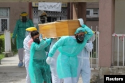 FILE - Health workers wearing protective gear move a body of a man who died from the coronavirus disease (COVID-19), outside an isolation ward at the Ayub Teaching Hospital in Abbottabad, Pakistan, April 16, 2020.