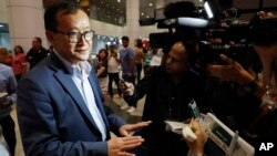 Cambodia's exiled opposition leader Sam Rainsy, left, speaks to the media as he arrived at Kuala Lumpur International's Airport in Sepang, Malaysia Saturday, Nov. 9, 2019.