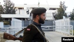FILE - A Pakistani soldier stands guard in front of the Indian High Commission in Islamabad, Feb. 8, 2003.