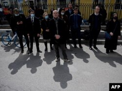 FILE - Diplomats from various countries wait outside of the Dandong Intermediate People's Court, where the trial of Canadian businessman Michael Spavor is being held, in Dandong in China's northeast Liaoning province, March 19, 2021.