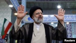 El candidato presidencial Ebrahim Raisi saluda después de emitir su voto durante las elecciones presidenciales en un colegio electoral en Teherán, Irán, el 18 de junio de 2021.