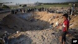 រូបឯកសារ៖ កុមារជនជាតិប៉ាឡេស្ទីនម្នាក់មើលទៅរណ្តៅមួយពីការវាយប្រហារដោយមីស៊ីលអ៊ីស្រាអែល ដែលបានបំផ្លាញផ្ទះមួយខ្នង និងសម្លាប់សមាជិកប្រាំបួននាក់នៃគ្រួសារមួយ នៅតំបន់ Gaza កាលពីថ្ងៃទី១៤ ខែវិច្ឆិកា ឆ្នាំ២០១៩។
