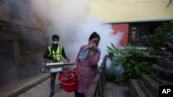 A Nepalese woman covers her face as a worker fumigates an area in an attempt to control mosquito-borne diseases in Kathmandu, Nepal, Sept. 5, 2019. The government says dengue cases has shot up by more than 65% across the country in the last week.