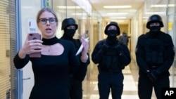 Aktivis oposisi Lyubov Sobol melaporkan secara langsung melalui telepon saat polisi berjaga-jaga selama penggerebekan di kantor Yayasan Anti-Korupsi, di Moskow, Rusia, 26 Desember 2019. (Foto: AP)