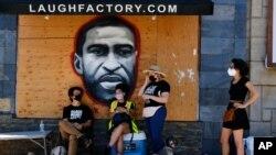 洛杉矶抗议者站在街边一副巨大的弗洛伊德壁画前面。
