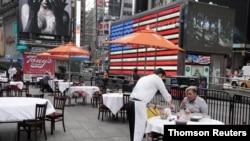 지난 12월 미국 뉴욕 타임스스퀘어의 야외 식당에서 종업원이 음식을 나르고 있다.