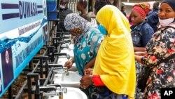 Les gens utilisent une station de lavage des mains installée pour les membres du public entrant sur un marché à Dodoma, en Tanzanie, le 18 mai 2020.