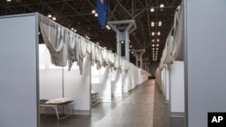 In this March 27, 2020 photo provided by Office of Governor Andrew M. Cuomo, makeshift hospital rooms stretch out along the floor at the Jacob Javits Convention Center in New York.