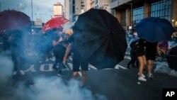 """Učesnici protesta u Hong Kongu """"brane"""" se kišobranima od suzavca, 28. jul 2019."""