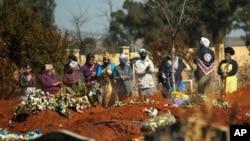 Para kerabat menghadiri pemakaman anggota keluarga mereka yang meninggal akibat Covid-19 di Johannesburg, Afrika Selatan (foto: dok).