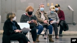 FILE - In this Jan. 20, 2021, file photo, people that received a COVID-19 vaccine socially distance as they wait the required fifteen minutes to monitor for adverse reactions after getting the shot at Fair Park in Dallas.