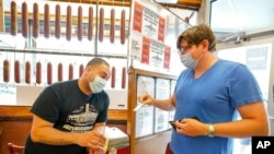 A Katz's Deli employee, left, checks the proof of vaccination from a customer who will be eating inside the restaurant, in New York, Aug. 17, 2021.